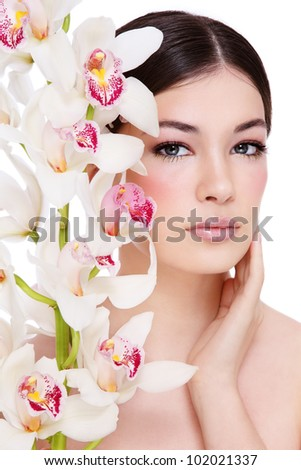 Young beautiful healthy girl with orchid on white background - stock photo