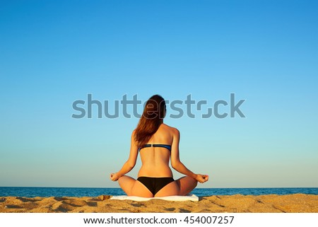 Young beautiful healthy woman doing meditation on the beach. Summer beach vacation, travel. - stock photo