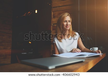 Young beautiful hipster girl with good mood is sitting with big notepad in coffee shop during her recreation time, charming Caucasian woman enjoying calm and rest after work on her laptop computer  - stock photo