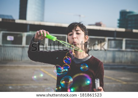 young beautiful hipster woman bubble blower in the city - stock photo