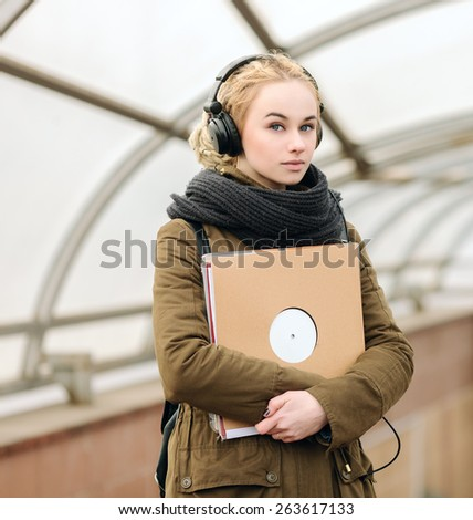 Young beautiful hipster woman in big dj headphones posing with a vinyl records on subway entrance - stock photo