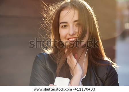 Young beautiful hipster woman listening music with headphones in the city. - stock photo