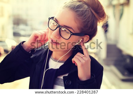 Young beautiful hipster woman listening music with headphones in the city. Photo toned style Instagram filters. - stock photo