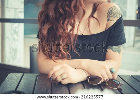 young beautiful hipster woman with red curly hair at the bar - stock photo