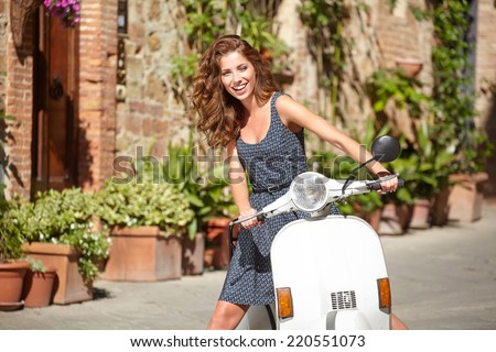 Young beautiful italian woman sitting on a italian scooter.  - stock photo