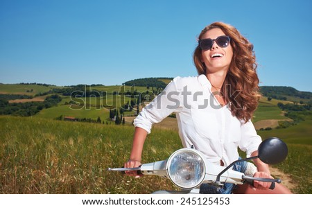 Young beautiful italian woman sitting on a italian scooter in tuscany outdoor  - stock photo