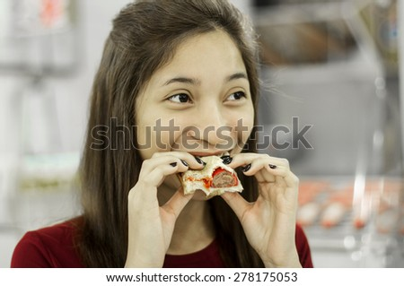 Young beautiful lady eating a hotdog sandwich. - stock photo