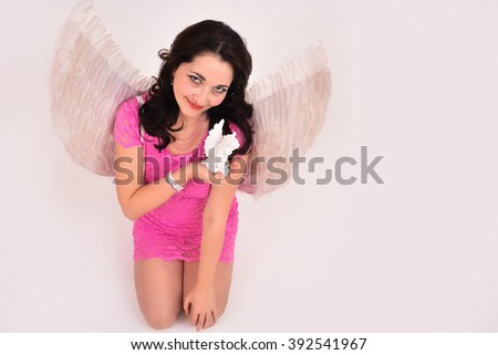 Young beautiful lady holding an angel with white wings - stock photo