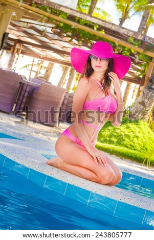 young beautiful lady in summer hat enjoying summer vacation in tropical resort near water pool, outdoor portrait - stock photo