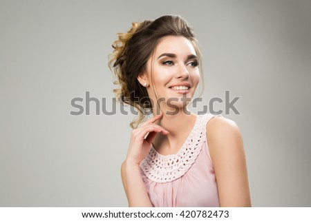 Young beautiful lady in tender pink dress posing in studio on grey background. not isolated.Supple wedding make up hairstyle and neutral lips.Gorgeous spring portrait. Charming face and stunning smile - stock photo