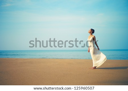 Young beautiful lady in white dress on the beach - stock photo