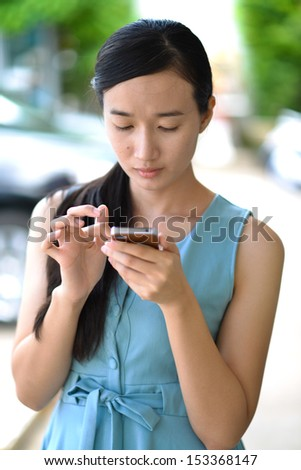 Young beautiful lady touching and browsing her smart phone - stock photo
