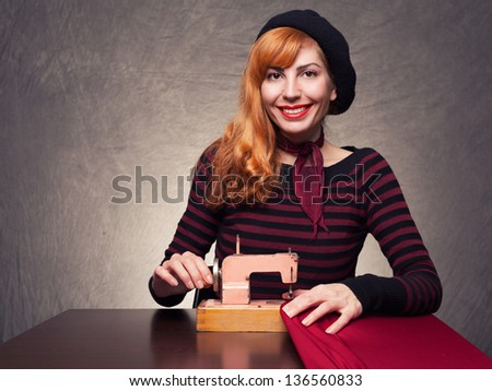 young beautiful lady with a retro sewing machine looking at you on grunge background - stock photo
