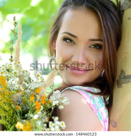 young beautiful lady with field flowers outdoor portrait, charming girl resting in summer park - stock photo