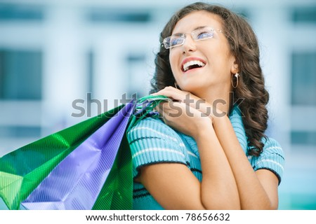 Young beautiful laughing woman in blue sweater with purchases from shop. - stock photo
