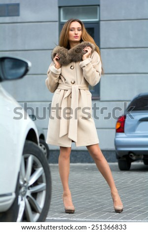 Young beautiful leggy chestnut in a white coat with a fur collar standing near the white car - stock photo