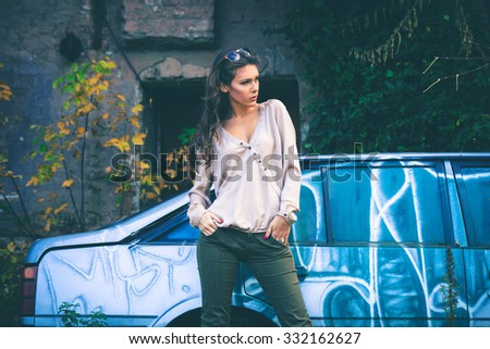 young beautiful long hair woman portrait with sunglasses , outdoor in the city, wearing shirt and pants in front of old car - stock photo