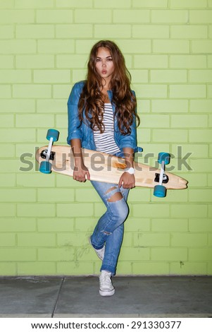 young beautiful long-haired brunette girl with wooden longboard skateboard coquettishly sending an air kiss to the camera near the green brick wall - stock photo