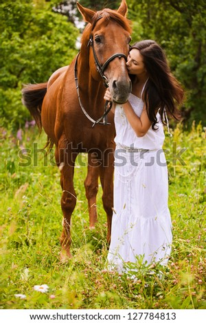 Young beautiful long-haired woman wearing white dress kissing brown graceful horse at summer green park. - stock photo