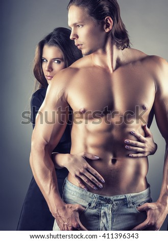 Young beautiful loving couple is embracing on a gray background - stock photo