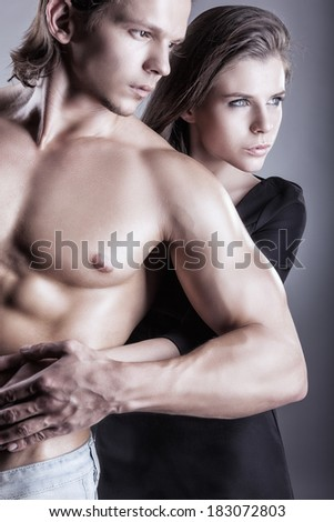 Young beautiful loving couple is embracing on a gray background. Focus on woman - stock photo