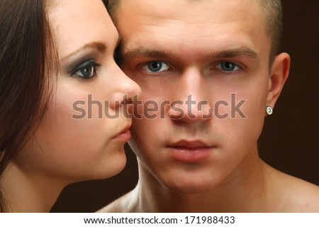 Young beautiful loving couple is embracing - on black background - stock photo