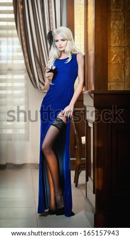 Young beautiful luxurious woman in long elegant dress. Beautiful young blonde woman in blue dress holding a glass of wine. Seductive blonde woman in luxury manor, vintage style - stock photo