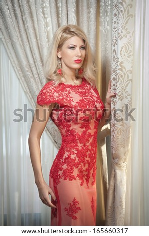 Young beautiful luxurious woman in long elegant dress. Beautiful young blonde woman in red dress with curtains in background. Seductive blonde woman with red lace dress in luxury manor, vintage style - stock photo