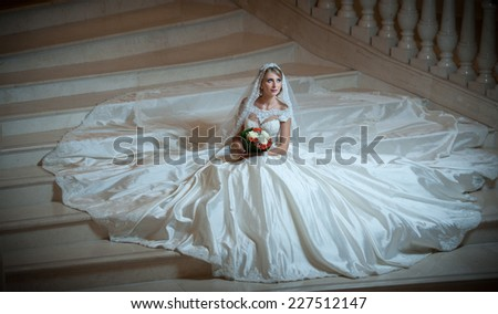 Young beautiful luxurious woman in wedding dress sitting on stair steps in semi-darkness. Bride with huge wedding dress holding her bouquet. Seductive blonde bride with gorgeous gown posing - stock photo