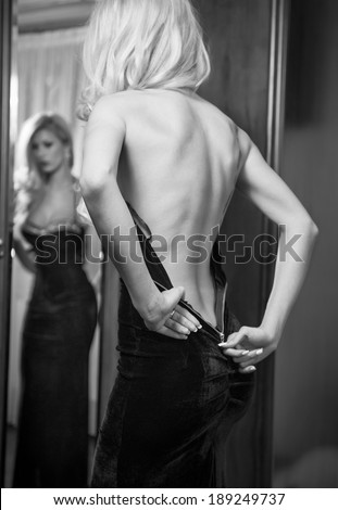 Young beautiful luxurious woman zipping up her long elegant black dress looking in a large mirror. Back side view, black and white photo. Seductive blonde woman in luxury manor, vintage style - stock photo