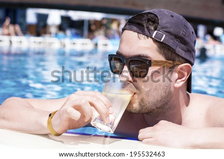young beautiful man drinking cocktail in a summer pool - stock photo