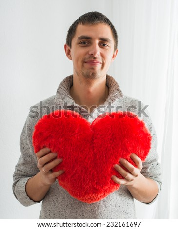 Young beautiful man with heart in his hand - stock photo