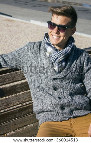 Young beautiful man with sunglasses smiling sitting on a bench - stock photo