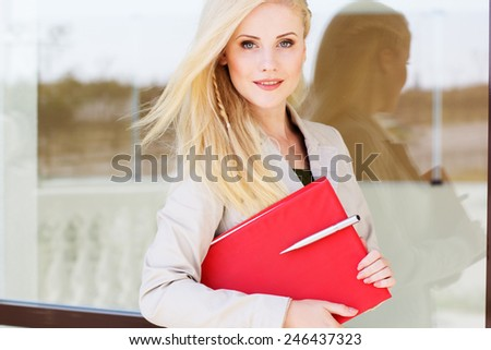 Young beautiful manager girl is holding pen and red folder - stock photo