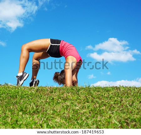 young beautiful mixed race girl doing yoga warrior pose on a beautiful day with clear blue sky. Pretty african american female performing relaxation exercise on a nice spring day. copy space. - stock photo