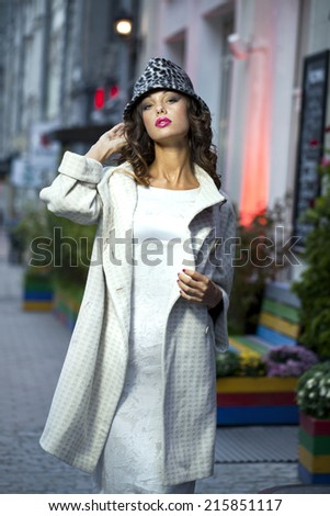 Young beautiful model in a stylish designer clothes posing on the street in the evening - stock photo