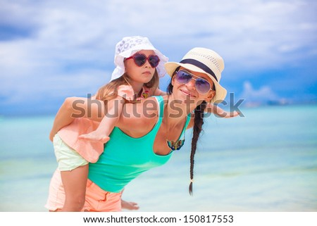Young beautiful mother and her adorable little daughter have fun at tropical beach - stock photo