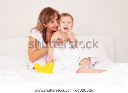 young beautiful mother and her baby on the bed at home after the shower - stock photo