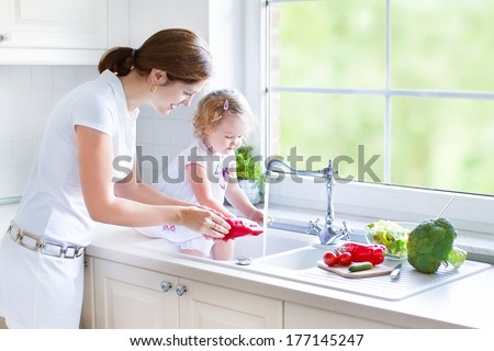 Young beautiful mother and her cute curly toddler daughter washing vegetables together in a kitchen sink getting ready to cook salad for lunch in a sunny white kitchen with a big garden view window - stock photo