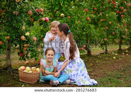 Young beautiful mother and her daughters picking fresh organic apples on a farm - stock photo