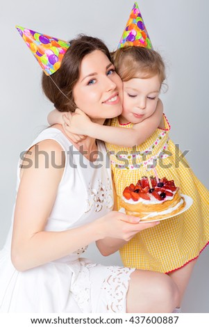 young beautiful mother and her little daughter are celebrating a birthday.  cake with candles. happy birthday baby - stock photo
