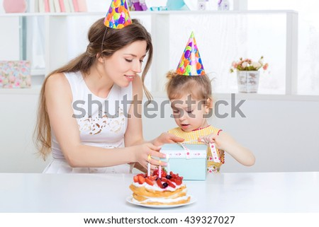 young beautiful mother and her little daughter are celebrating a birthday. on the table is a cake with candles. happy birthday baby. mom gives daughter gift - stock photo