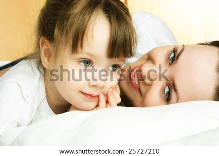 young beautiful mother and her little dreamy daughter in bed - stock photo