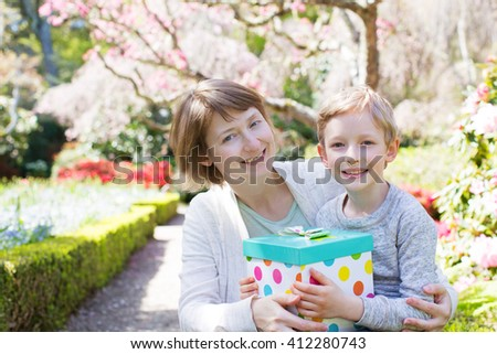 young beautiful mother and her little son giving her a gift for mother's day enjoying time together at spring time in the park - stock photo