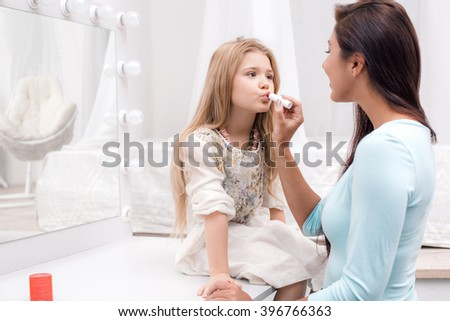 Young beautiful mother and little daughter while applying makeup. Nice cozy bedroom. Mother helping daughter to use lipstick - stock photo