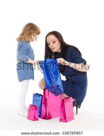 Young beautiful mother and sweet little daughter with shopping bags on a white background. Shopping family. - stock photo