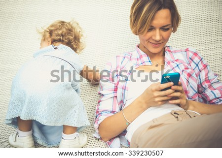 Young beautiful mother checks messages on her smartphone while her daughter has fun. Toned image - stock photo