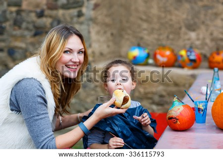 Young beautiful mother feeding her little daughter, adorable kid girl with hot dog or German sausage on thanksgiving or halloween pumpkin festival, outdoors. Family enjoy warm autumn day. - stock photo