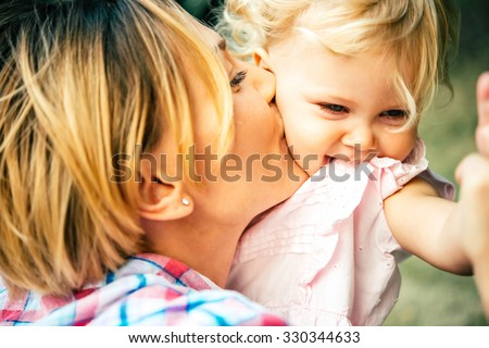 Young beautiful mother has fun with her daughter - stock photo