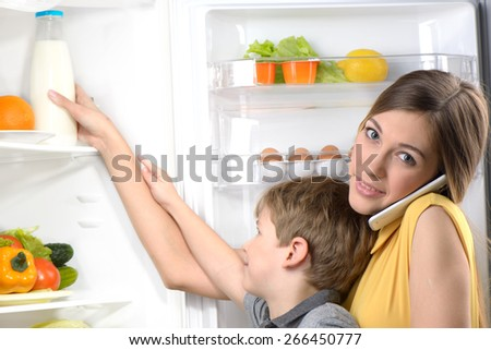 Young beautiful mother helping her little son to pick bottle of milk from fridge while using phone. Vegetables and fruits in the refrigerator - stock photo